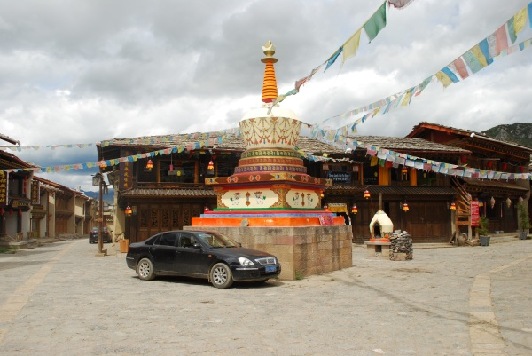 Car parked in one of the Old Town squares next to a stupa.